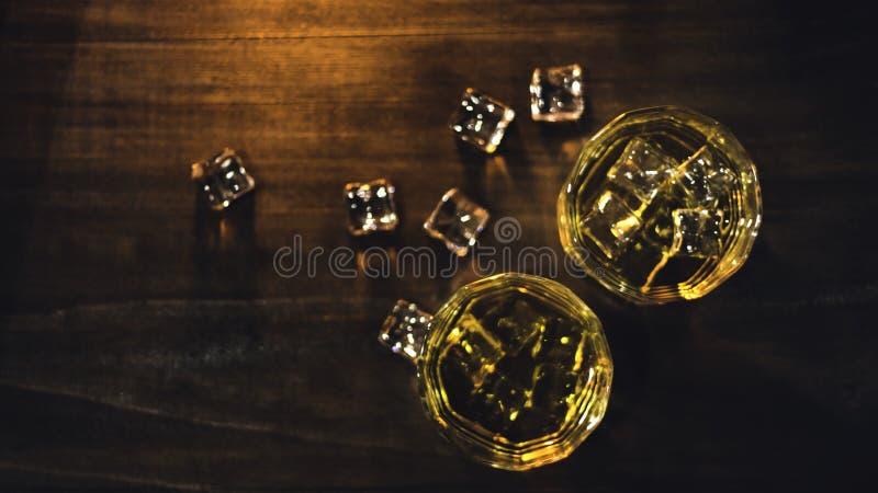Uísque da vista superior no vidro com o gelo ambarino bonito, colocado em uma tabela de madeira com uma superfície áspera contra  fotografia de stock royalty free