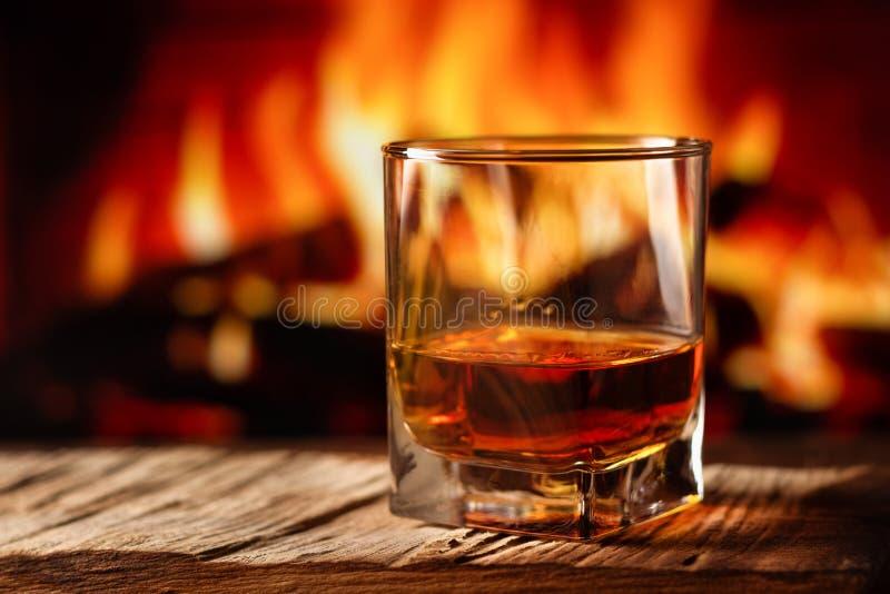 Uísque em um vidro com fogo na chaminé no fundo imagens de stock