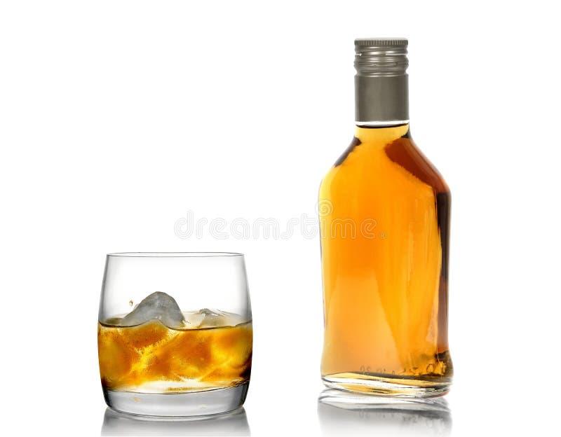Uísque em um vidro (com um gelo) e em um frasco (2) imagem de stock