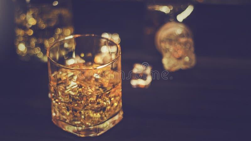 Uísque no vidro com o gelo ambarino bonito, colocado em uma tabela de madeira com uma superfície áspera contra um fundo e um boke imagem de stock