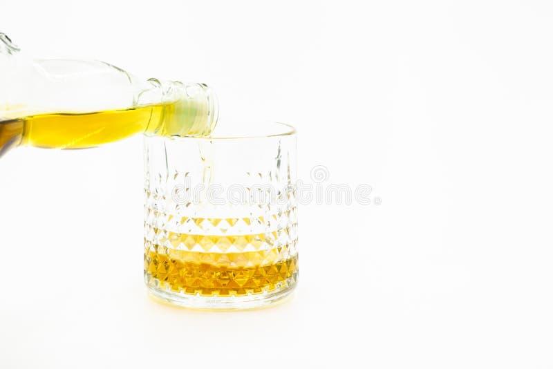 Uísque nos vidros da bebida alcoólica da bebida do uísque, uísque de derramamento nos vidros no fundo branco imagem de stock
