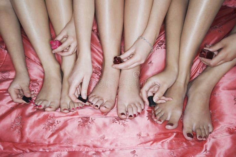 Uñas del pie de la pintura en Bedsheet rosado fotografía de archivo
