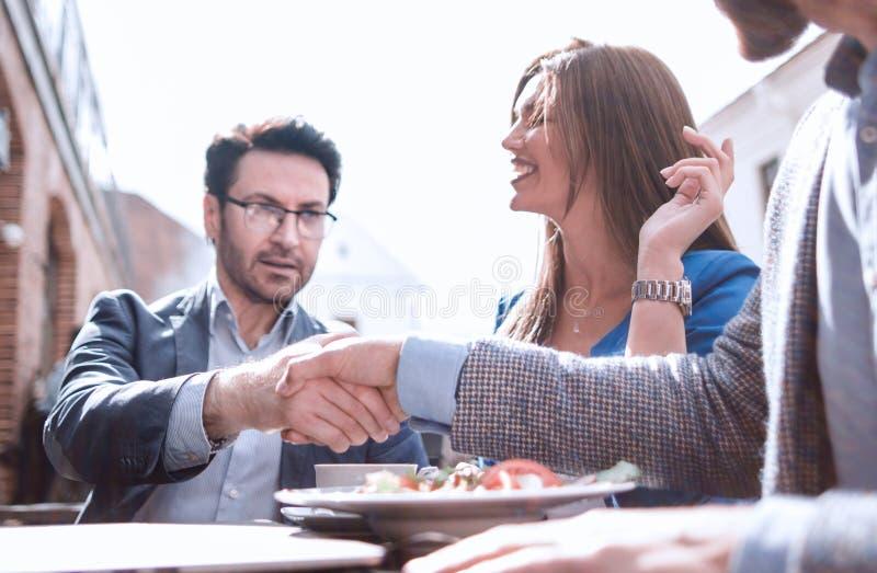 Uścisków dłoni koledzy przy stołem w ulicznej kawiarni fotografia royalty free