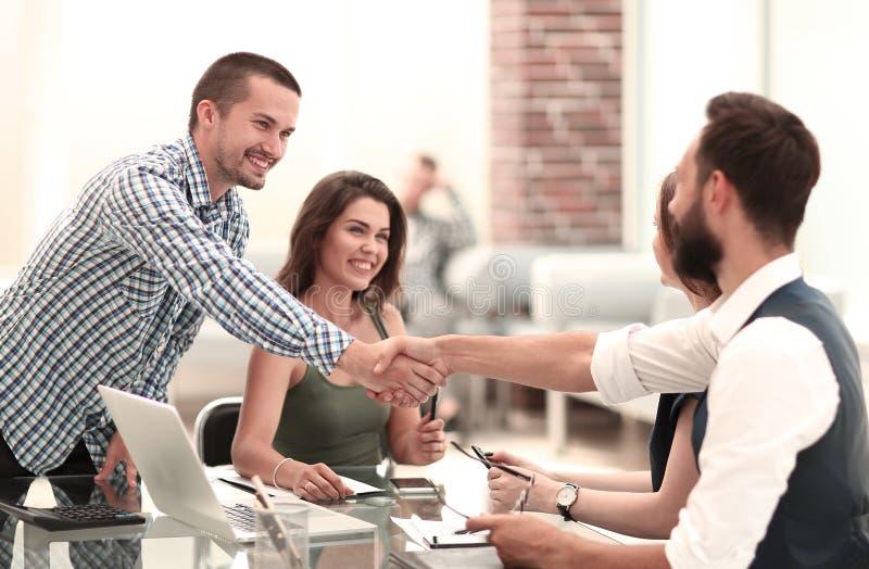 Uścisków dłoni partnery biznesowi nad biurkiem w biurze fotografia royalty free