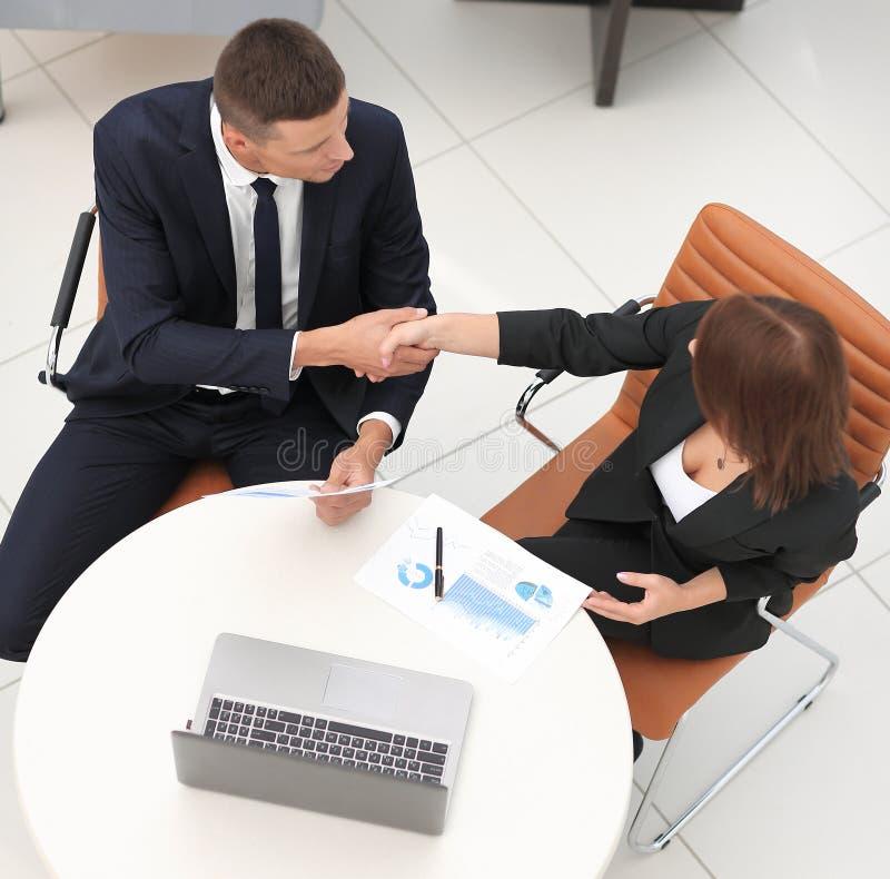 Uścisków dłoni partnery biznesowi po dyskusi pieniężni dokumenty obraz stock