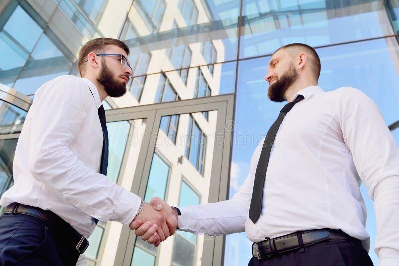 Uścisk dłoni dwa młodego człowieka przeciw kondygnaci biura buildin zdjęcie stock