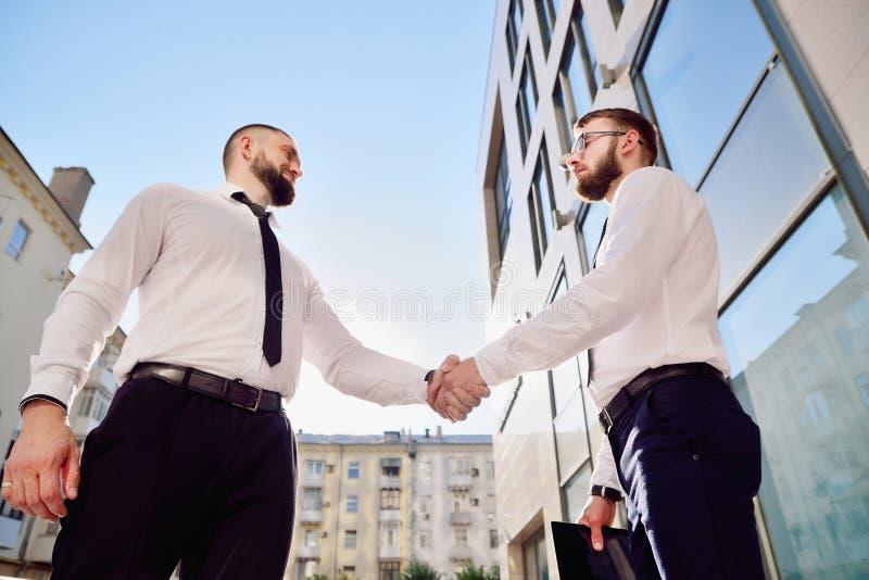 Uścisk dłoni dwa młodego człowieka przeciw kondygnaci biura buildin fotografia stock