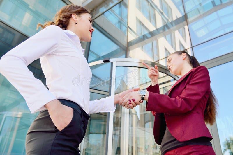 Uścisk dłoni dwa młodej dziewczyny przeciw tłu wielo- zdjęcie stock