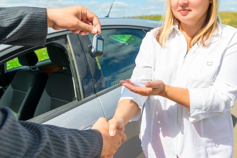 Uścisk dłoni i wręczać nad kluczami samochód zdjęcia royalty free