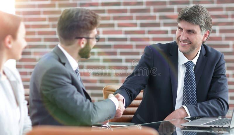 Uścisk dłoni koledzy przy biurkiem zdjęcia royalty free
