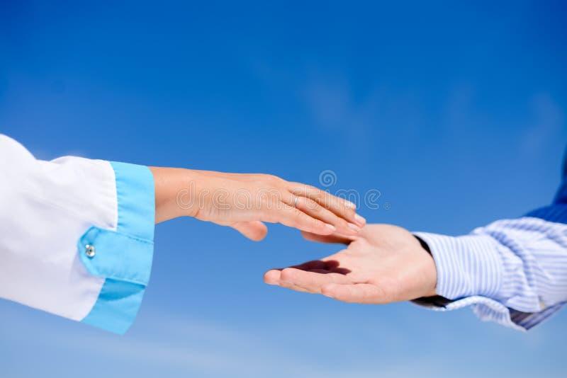 Uścisk dłoni między mężczyzna i lekarką nad niebieskim niebem zdjęcie royalty free