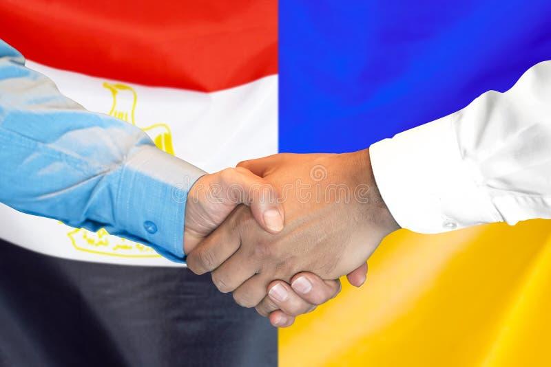 Uścisk dłoni na Egipt i Ukraina fladze tło obraz stock