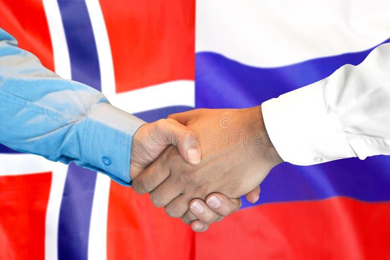Uścisk dłoni na Norwegia i Rosja fladze tło zdjęcie royalty free