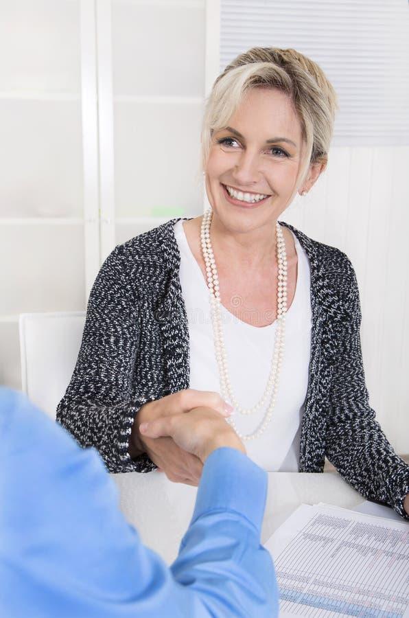 Uścisk dłoni pod dwa biznesową kobietą przy biurem fotografia stock