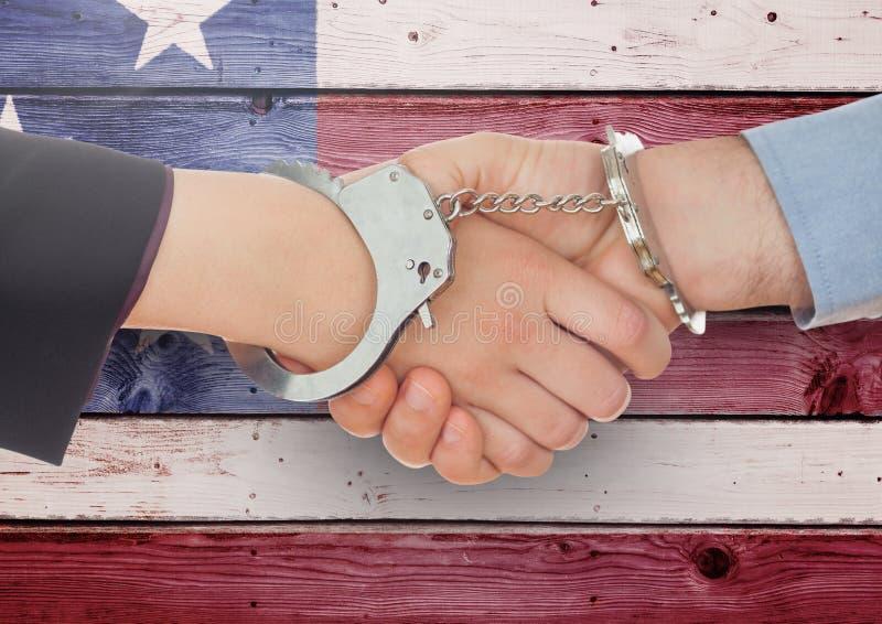 Uścisk dłoni z kajdankami przeciw drewnianemu flaga amerykańskiej tłu fotografia royalty free