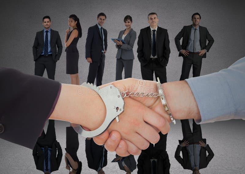 Uścisk dłoni z kajdankami przed ludźmi biznesu w popielatym pokoju zdjęcia royalty free