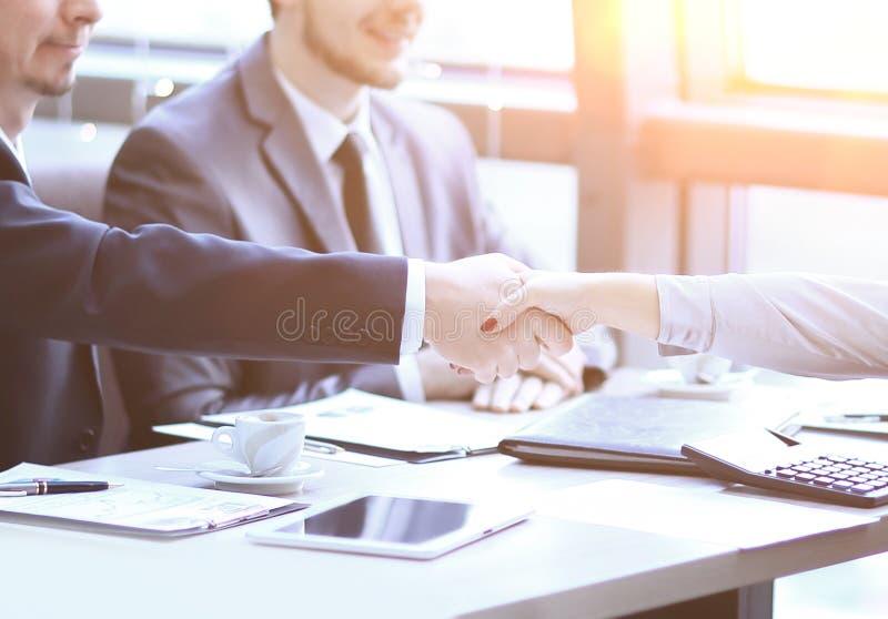 Uścisku dłoni kierownik i klient nad biurkiem obraz stock