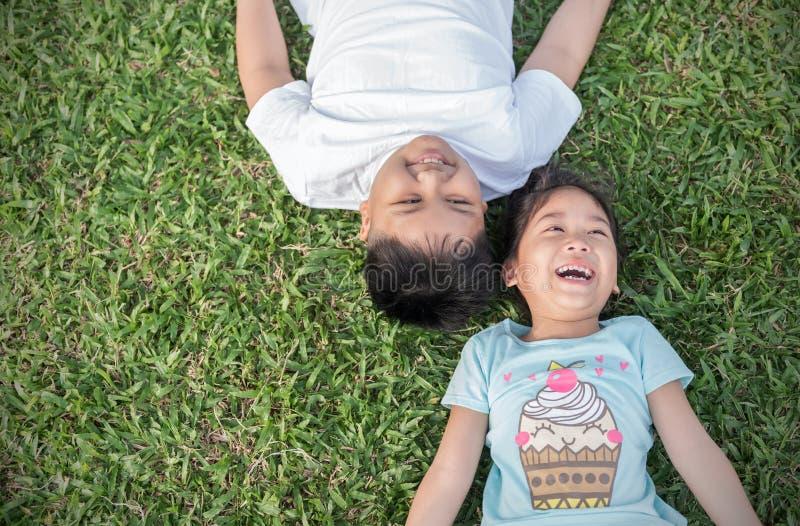 Uśmiechów dzieci kłamają puszek na trawie obrazy royalty free