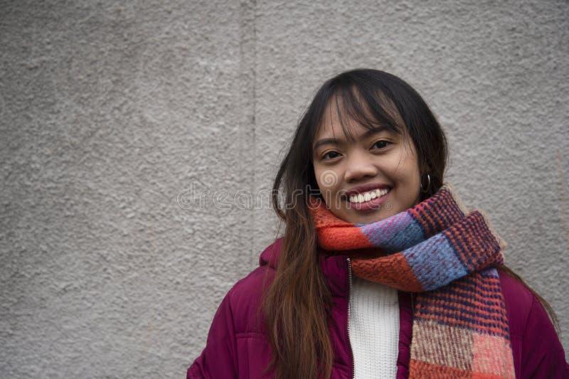 Uśmiech kobiety Filipiński młody nastoletni Azjatycki portret z czerwonym żakietem i szalikiem z popielatym ściennym tłem zdjęcie stock