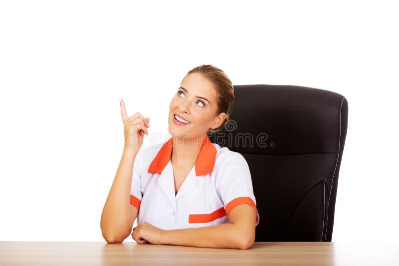 Uśmiech kobiety lekarki obsiadanie za biurkiem i wskazywać up zdjęcia royalty free
