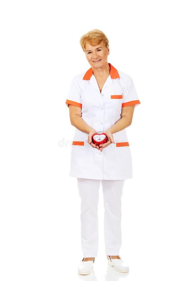Uśmiech kobiety starsza lekarka lub pielęgniarka trzymamy budzika zdjęcia royalty free