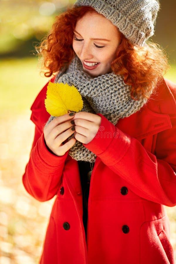Uśmiech rudzielec dziewczyny spojrzenia koloru żółtego liść zdjęcia stock