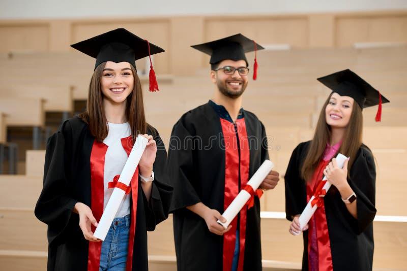 Uśmiechać się absolwentów utrzymuje dyplomy przed drewnianymi biurkami obrazy stock