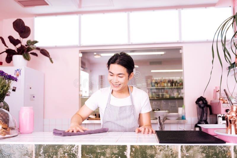 Uśmiechać się doświadczonego barmanu czyści jego miejsce pracy obraz stock