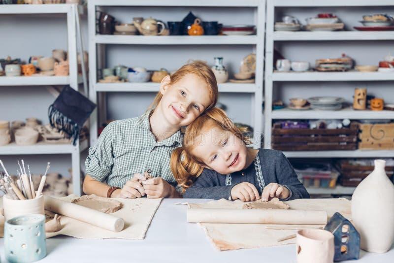 Uśmiechać się dosyć miedzianowłosych dzieciaków cieszy się ich czas przy sztuki studiiem obrazy royalty free