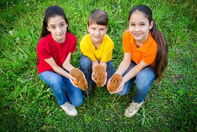 Uśmiechać się dzieciaków trzyma troszkę króliki przy zieloną trawą, Easter przeciw obraz royalty free