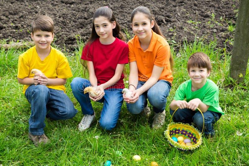 Uśmiechać się dzieciaków trzyma troszkę kurczaki przy zieloną trawą, Easter co zdjęcia royalty free