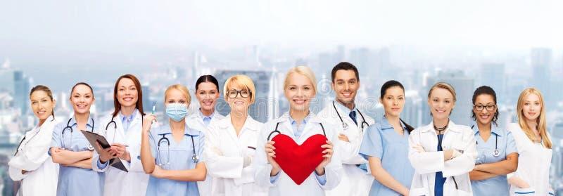Uśmiechać się lekarki i pielęgniarki z czerwonym sercem obrazy stock