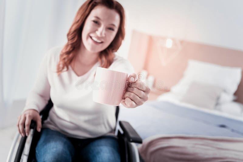 Uśmiechać się niepełnosprawnej kobiety pije kawę obrazy stock