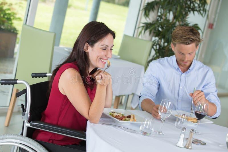 Uśmiechać się niepełnosprawnej kobiety z mężem przy restauracją obrazy stock