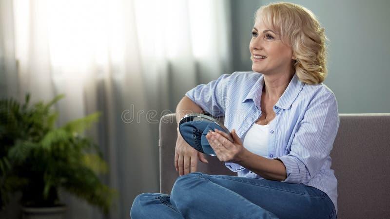 Uśmiechać się starzejącą się damy siedzącą kanapę z ręki lustrem, żeńska skóry opieka, kosmetologia obraz royalty free