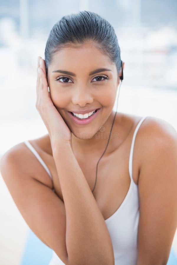 Uśmiechać się stonowaną brunetkę słucha muzyka obrazy stock