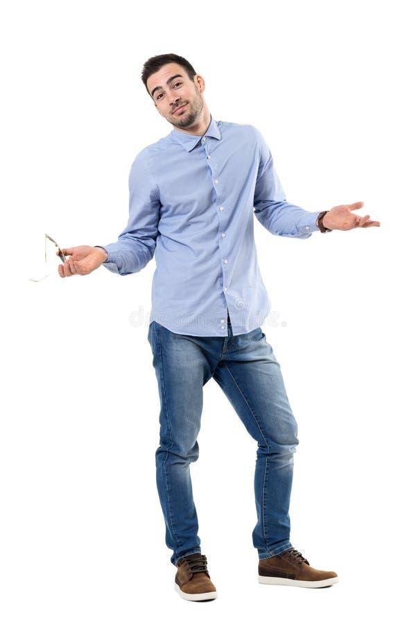 Uśmiechać się zmieszanego biznesmena wzrusza ramionami ramiona patrzeje kamerę obraz stock