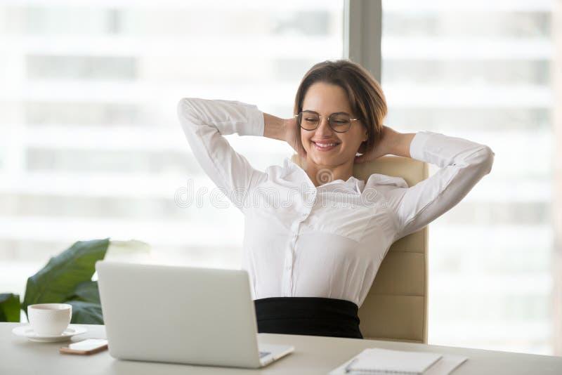 Uśmiechać się zrelaksowanego bizneswomanu ogląda śmiesznego online wideo przy wor fotografia stock