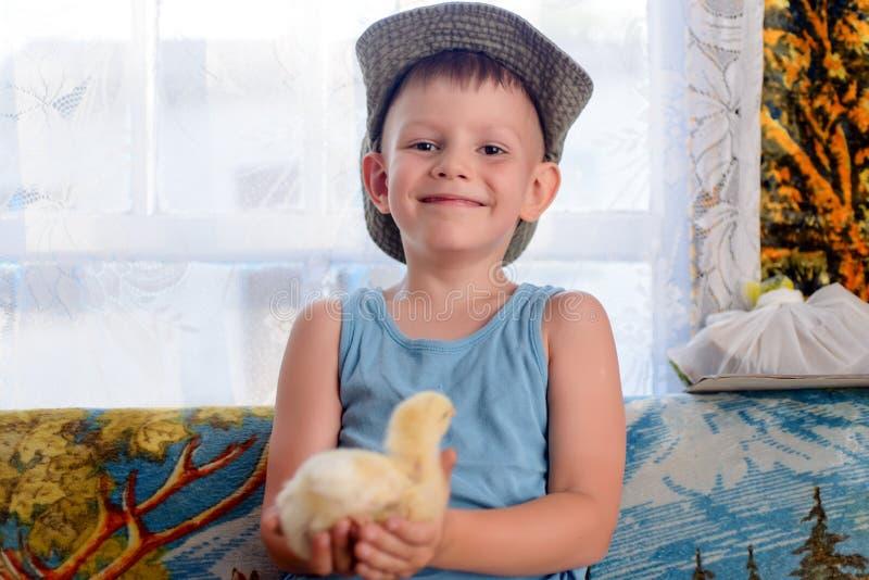 Uśmiecha się Ślicznej Młodej chłopiec Trzyma jego Pisklęcego zwierzęcia domowego zdjęcie royalty free