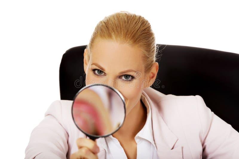 Uśmiecha się biznesowej kobiety obsiadanie za biurkiem i patrzeć w powiększać - szkło zdjęcia stock