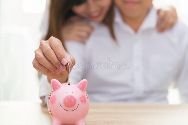 Uśmiecha się pary stawia monetę w różowego prosiątko banka na drewnianym des obraz stock