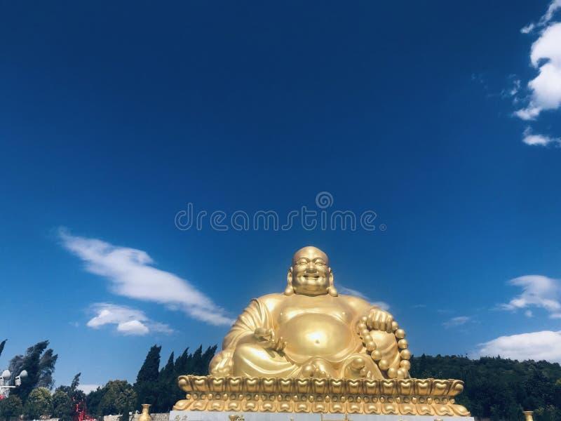 Uśmiechający się Buddha maitreyaï ¼ ŒUnder i białego cloudsï ¼ Œ niebieskie niebo obrazy royalty free