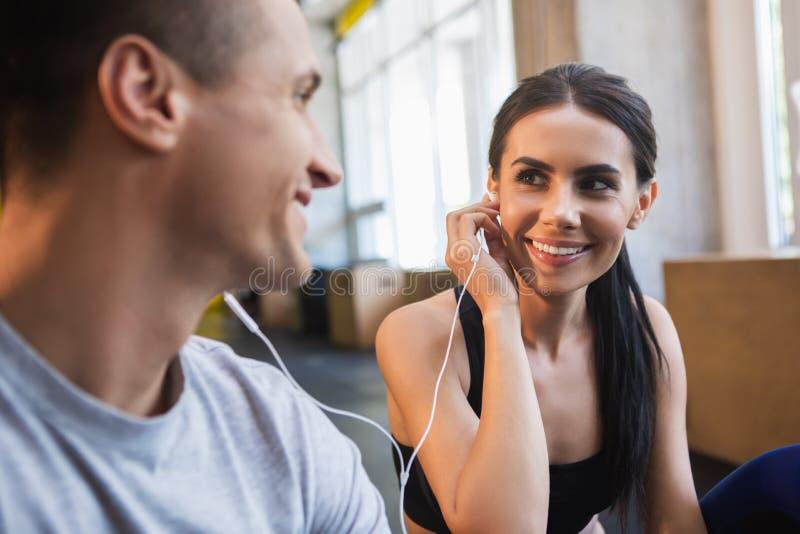 Uśmiechający się dama używa słuchawki z chłopakiem indoors obrazy stock