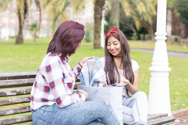 Uśmiechający się dwa kobiety pokazuje jej nowego odziewa jej przyjaciel obraz royalty free