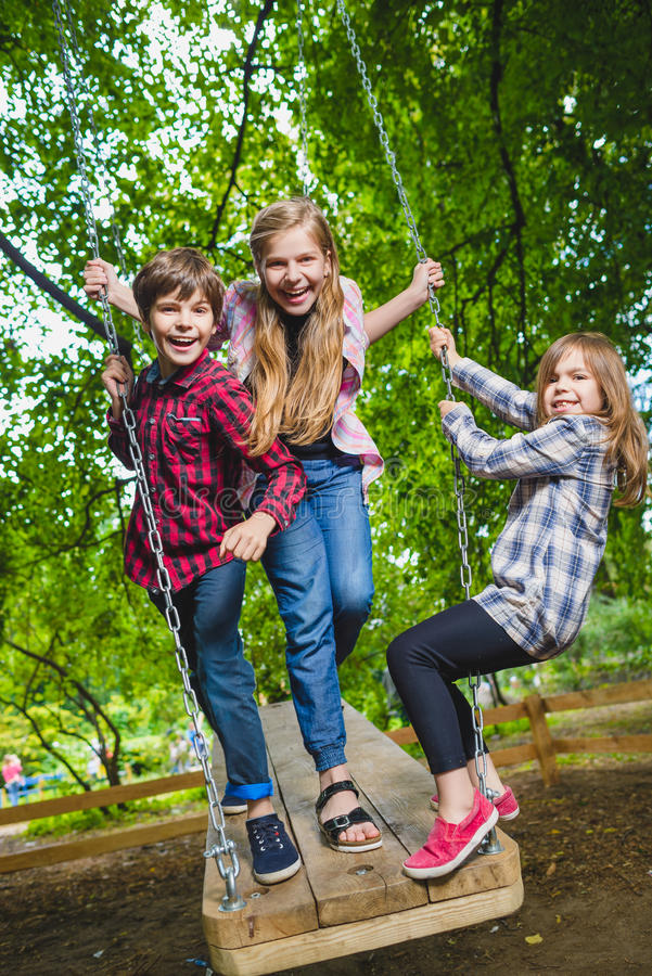Uśmiechający się dzieciaków ma zabawę przy boiskiem Dzieci bawić się outdoors w lecie Nastolatkowie jedzie na huśtawkowym outside zdjęcia royalty free