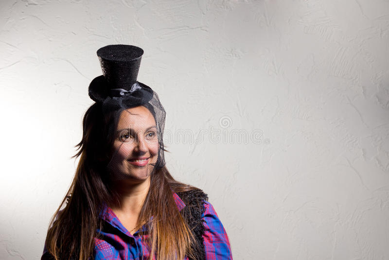 Uśmiechający się kobieta jest ubranym partyjnego odgórnego kapelusz fotografia royalty free