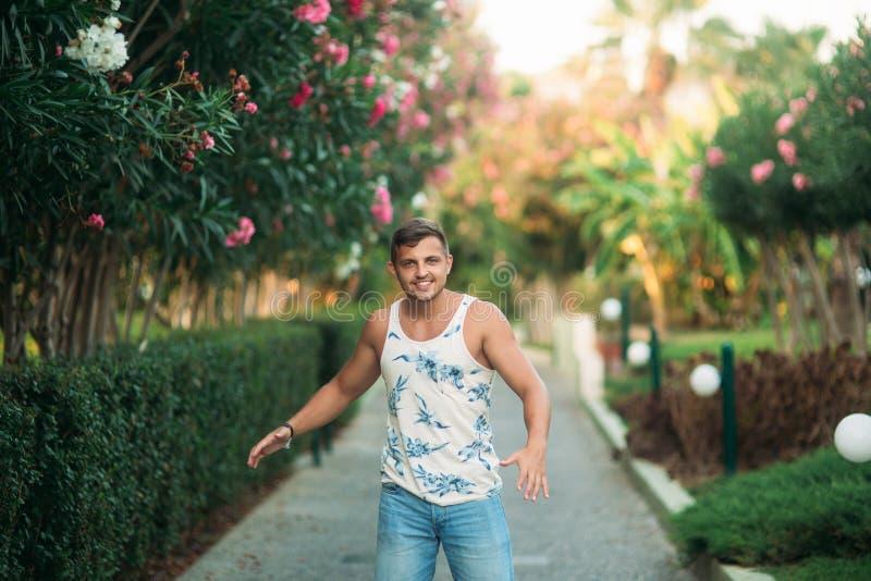 Uśmiechający się mężczyzna w skrótach i koszula w lato czasie chodzi blisko parka obraz royalty free
