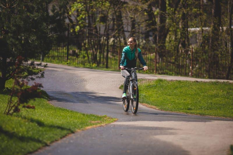 Uśmiechający się młoda dama jeździć na rowerze w parku zdjęcie royalty free