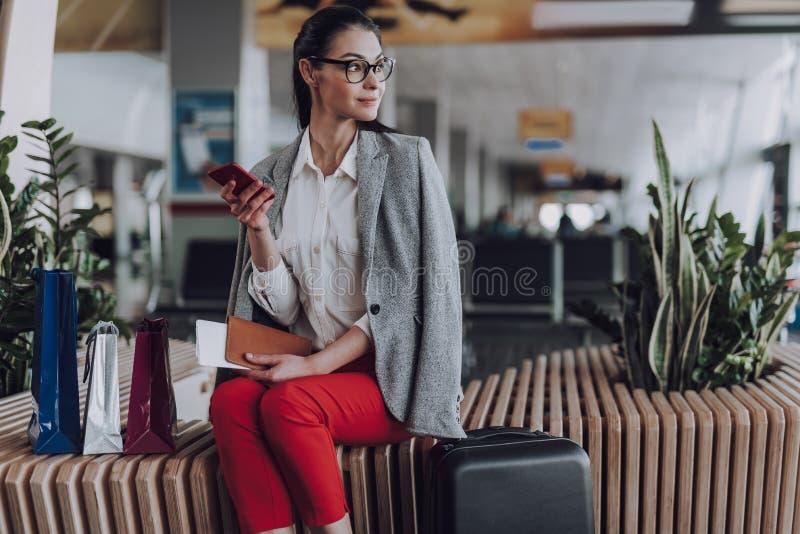 Uśmiechający się młoda kobieta z telefonem i bagażem w lotnisku zdjęcie stock