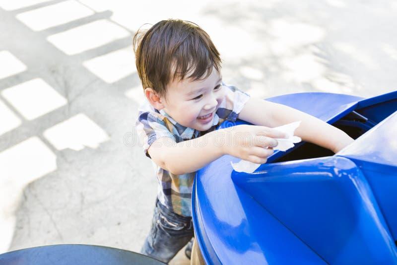 Uśmiechający się Mieszającej Biegowej chłopiec Umieszcza papier W Przetwarza kosz obraz stock
